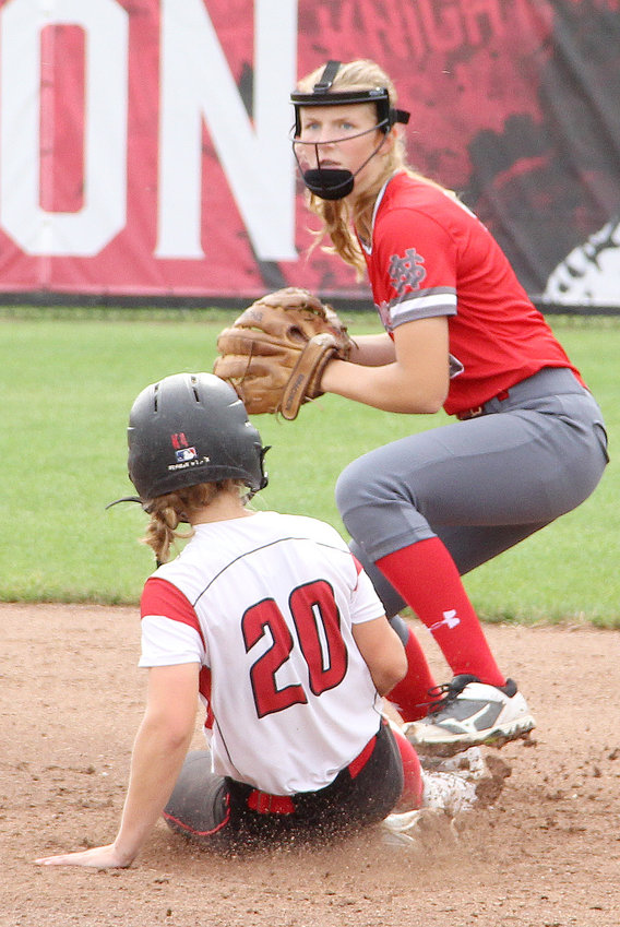 Lancer sophomore Kate Hayes looks to first base after getting the force out on a sliding Katie Anderson in the first game of Thursday's doubleheader with Davenport Assumption.