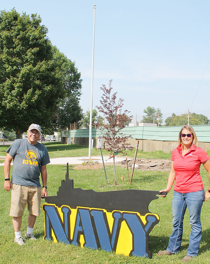 Organizers Bill Koellner and Gretchen Nollman show off the Navy mural saluting service members. It is one of five murals saluting veterans who served in the Army, Marines, Coast Guard and Air Force as well being built around a new flag pole on the fairgrounds.