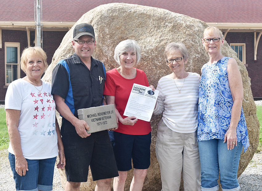 Rock to be painted in 2020—The Muscatine County Freedom Rock site in front of the historic Wilton Depot has begun efforts to populate the display with 1,000 pavers that honor the active and inactive service veterans of Muscatine County.  The Freedom Rock is scheduled to be painted in June of 2020. Shown above are the family members of the late Louis Brammeier of Wilton. From left are Sue Bruns; Doug Brammeier, holding a sample paver; Cindy Tietz, American Legion Auxiliary representative accepting the family's paver application; Faye Brammeier; and Cherie Brammeier. The Brammeiers were the first family to purchase a paver honoring their late father and husband, who served in the United States Army from 1950 to 1952. Interested parties who would like to participate in this effort can visit www.muscatinecountyfreedomrock.com to view the different sized pavers that are available and print out paver application forms. Forms are also available at the Wilton-Durant Advocate News office in Wilton and the West Liberty Index office.