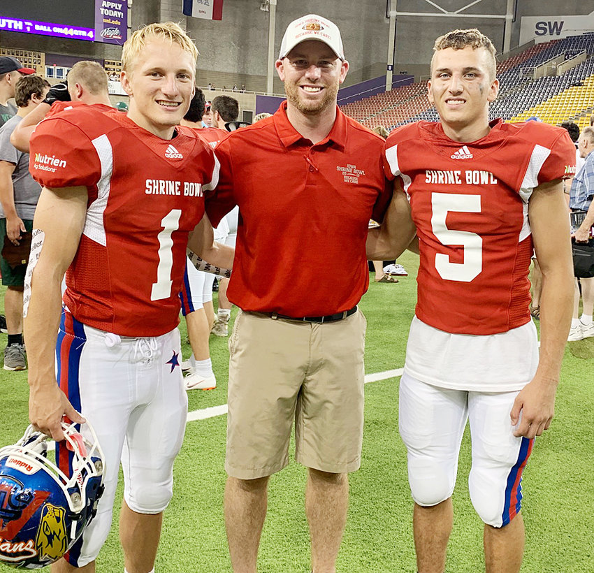Wilton's Jerome Mays (left) and Durant's Mason Compton (right) are shown with Wilton head coach Ryan Hetzler on the field at the UNI Dome at the 2019 Shrine Bowl July 20. Hetzler served on the South team coaching staff and Mays and Compton played for the winning South team. Compton had a touchdown catch in the game as the South won 24-13.