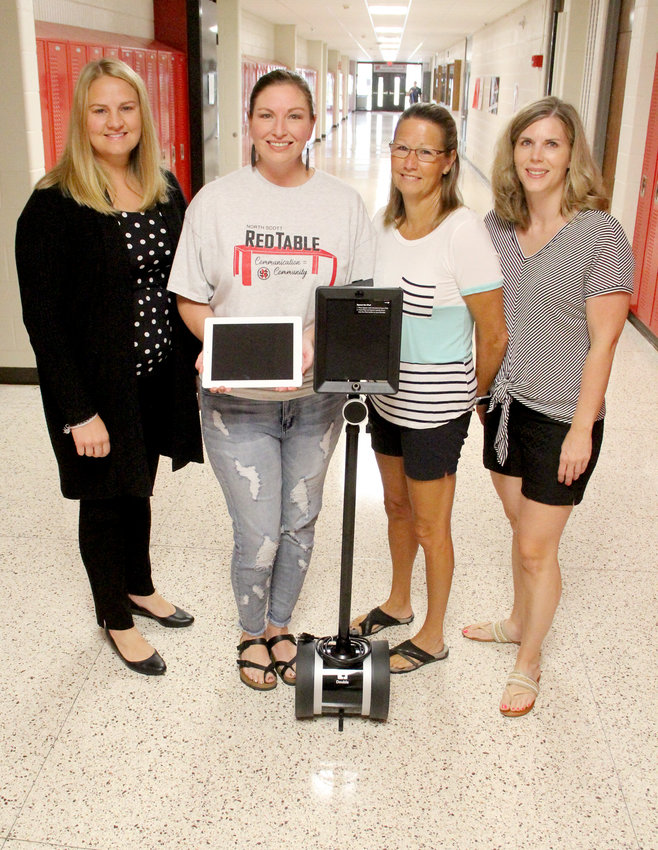 Molly Bergfeld, April Rus, Jodie Brotherton and Kim Ranson pose at the junior high with an iPad and a Double robot that connects students at home with their classes.