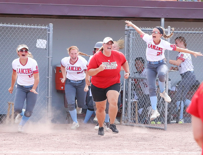 Sophomore Kaylee Gerardy (22), assistant coach Christy Haynes and sophomore Taylor Robertson can't contain their excitement after Kate Hayes scored the winning run.