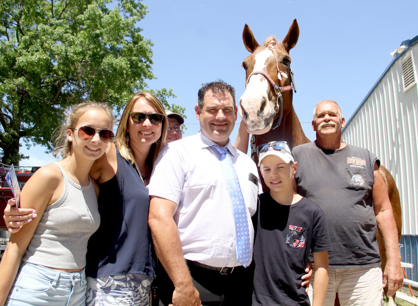 Mississippi Valley Fair horse judge Ryan Black is surrounded by family and friends, from left, daughter Campbell, wife Elaine, friend Steven Connell, Black, Black's son Sam and Dale McMain, of Delmar. Behind them is McMain's horse, Niva.