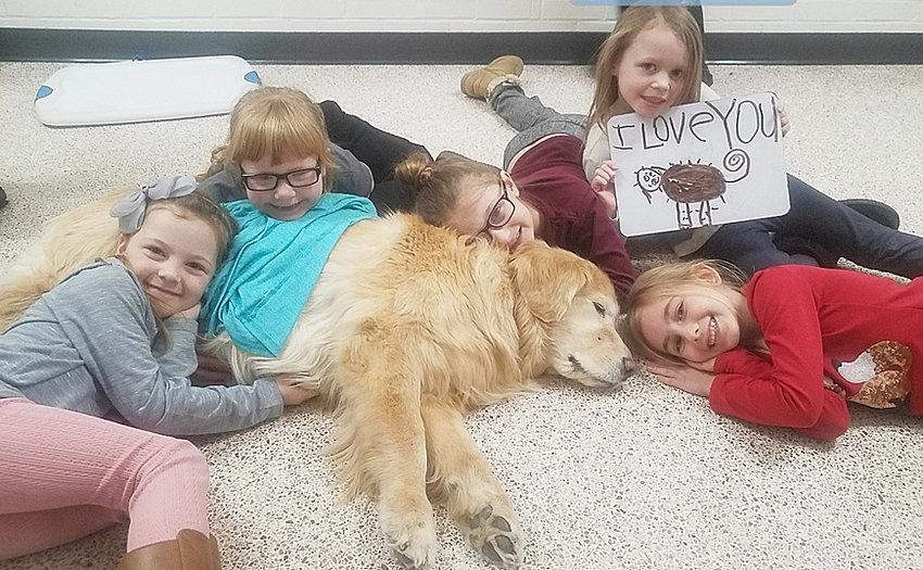 Sprite snuggles with Glenn Elementary students.
