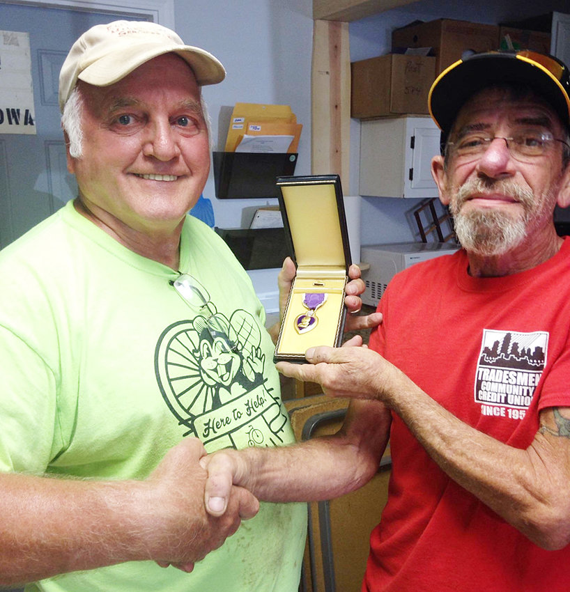 On Friday, July 19, the family of Dwaine Whitmer, formerly of Wilton, donated a purple heart to the Wilton American Legion Post 584. The Purple Heart was awarded to Whitmer after being shot during World War II. Pictured is a representative of the Whitmer family (right) who delivered the Purple Heart to Roger Bender (left) accepting the donation on behalf of the Wilton American Legion.