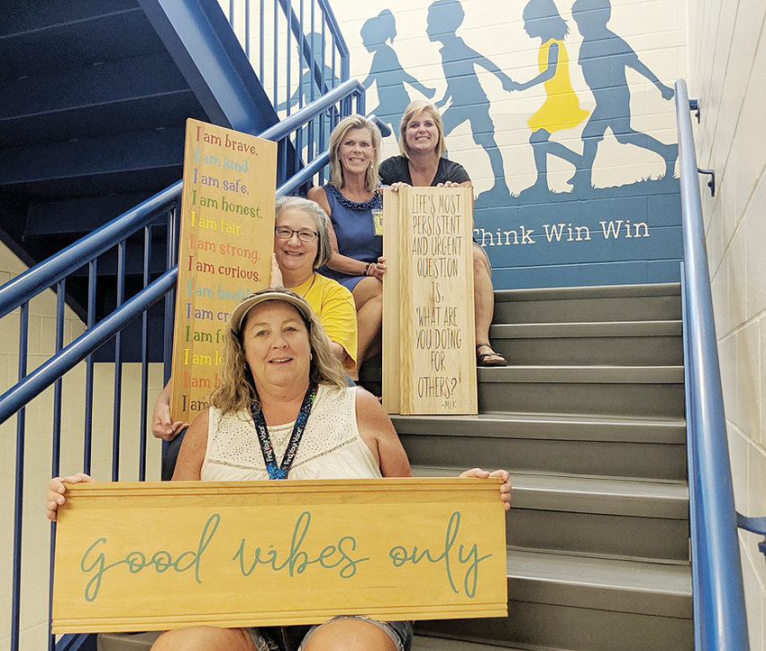 Wilton Elementary staff Jane Owens, Dory Smith, Denise Austin and Sara Anderson are shown with signs made from old library shelves. The stairwell mural was painted by local artist Robert Arlen.