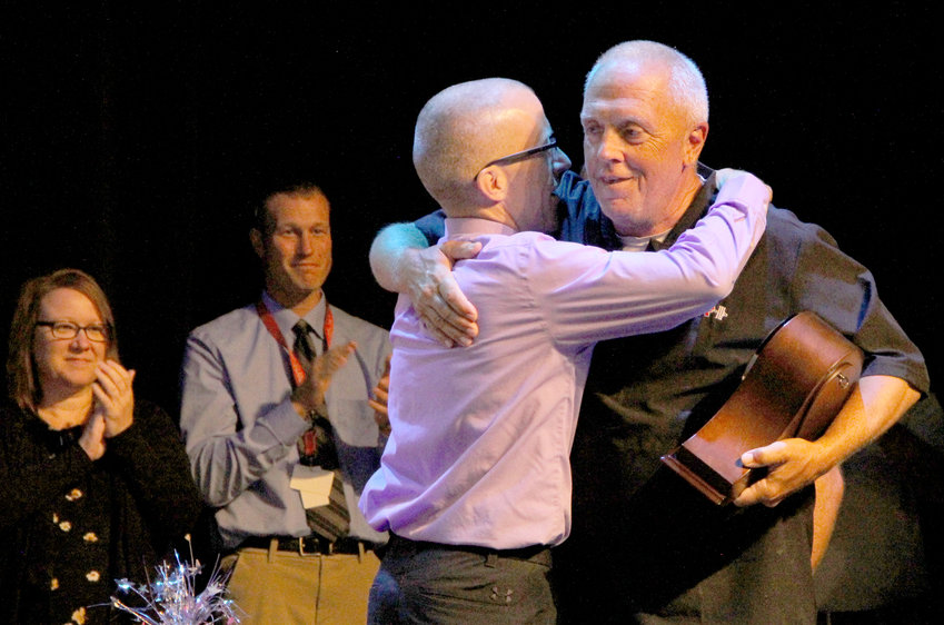 North Scott High School principal Shane Knoche embraces Richard Erps, who retired after 42 years as high school custodian.