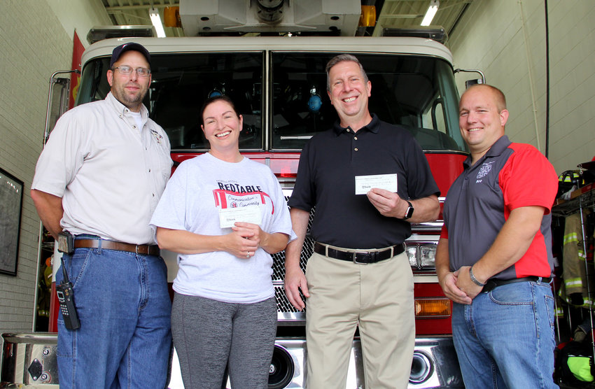 Night Out organizers April Rus and Long Grove Mayor Michael Limberg, center, present $500 checks to Eldridge Fire Chief Keith Schneckloth, left, and Long Grove Fire Chief Josh Roe, right. Contributions from the Aug. 6 event funded the donations.