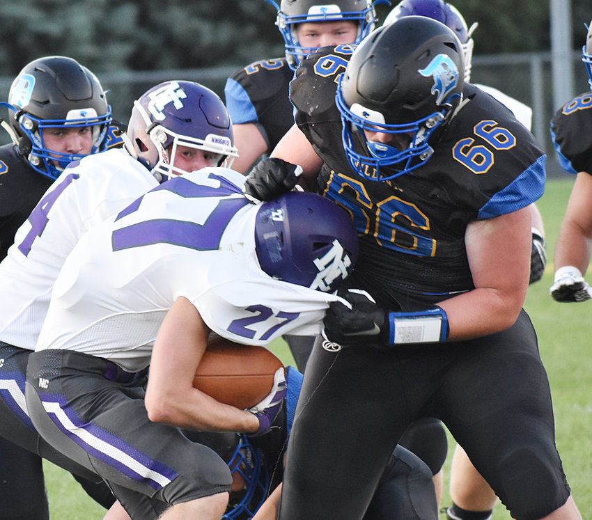 Durant's big Joe Lilienthal (right) wraps up North Cedar running back Brody Hawtrey during home action Sept. 6. The Wildcats were down 14-0 early before coming back to take a 22-16 lead in the fourth quarter. The Knights then put together one final drive to win 24-22 in the game's final minute.