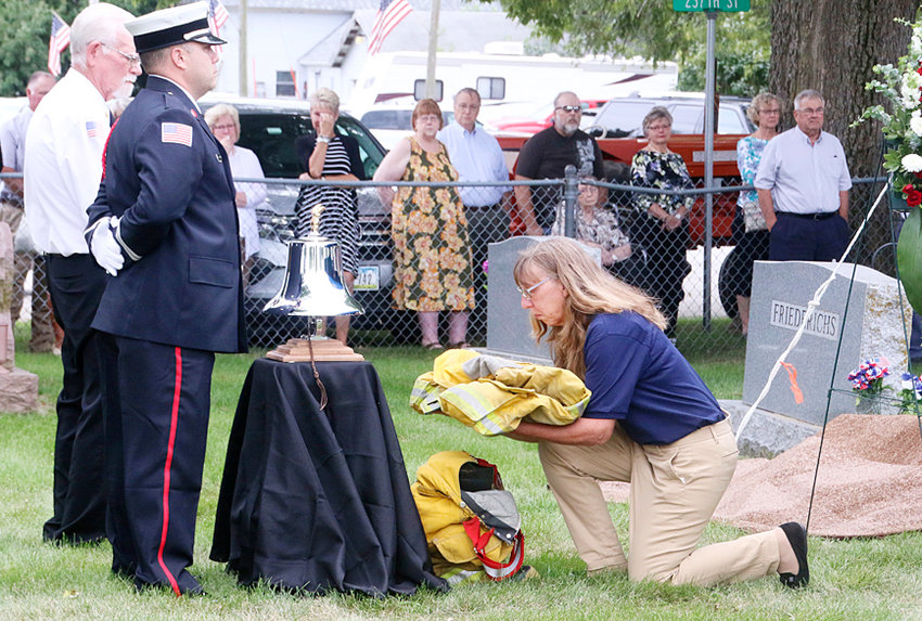 """Maysville firefighter Joyce Morrison places Chief Ty Arp's gear on top of his boots during the """"last call' ceremony."""