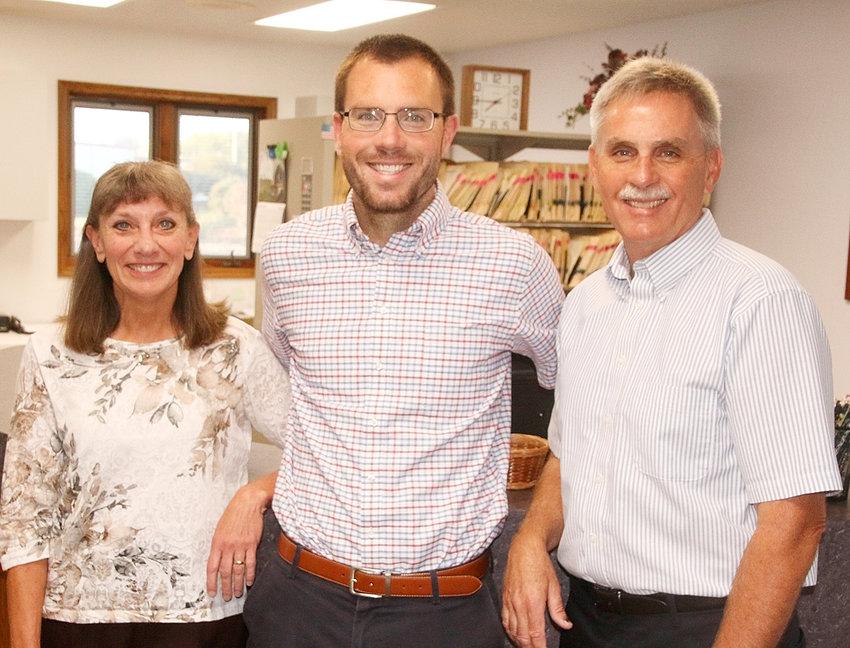 Greg Daniels, center, poses with parents, Drs. Julie and Scott Daniels.