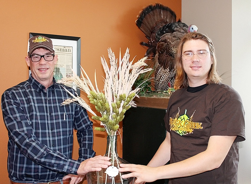 Buck Creek horticulturalist Christian Peterson, on right, and general manager Shawn Meaney show off a display of hops decorating their office in Solon. Hops are grown in seven Iowa locations including near West Liberty for the company, as well as two other farms just outside the state.
