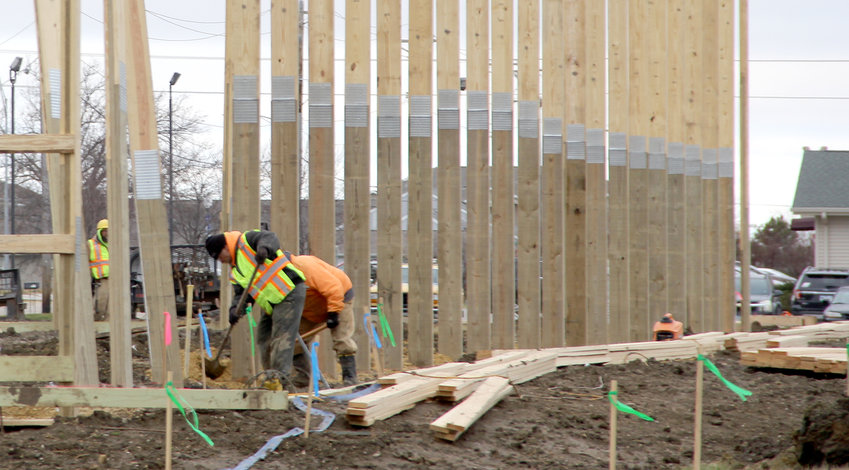 Workers secure the Wick Building frame for North Scott's indoor sports facility.