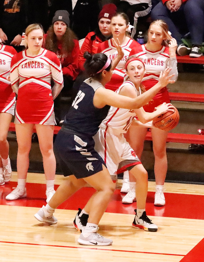Despite tough defense being displayed by Pleasant Valley's Ilah Perez-Johnson, Lancer senior Brooke Kilburg looked inside during first-half action of North Scott's 70-33 win over the Spartans on Tuesday (Dec. 10).