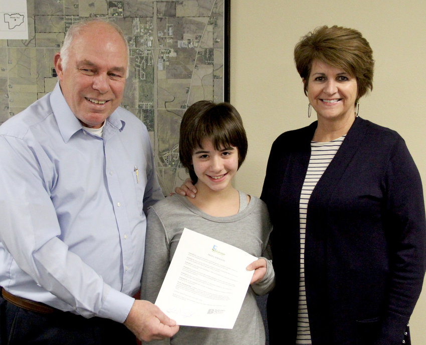 Karen VanDeCasteele, of Eldridge (r), and Mia Walters accept Eldridge mayor Marty O'Boyle's proclamation of January as mentoring month. VanDeCasteele met Walters through Big Brothers/Big Sisters and recently enjoyed making cookies and gingerbread houses together over the holiday. VanDeCasteele lauded the program and encouraged others to sign up, especially men. Sign up or learn more online at bbbsmv.org, or call (563) 323-8006 .