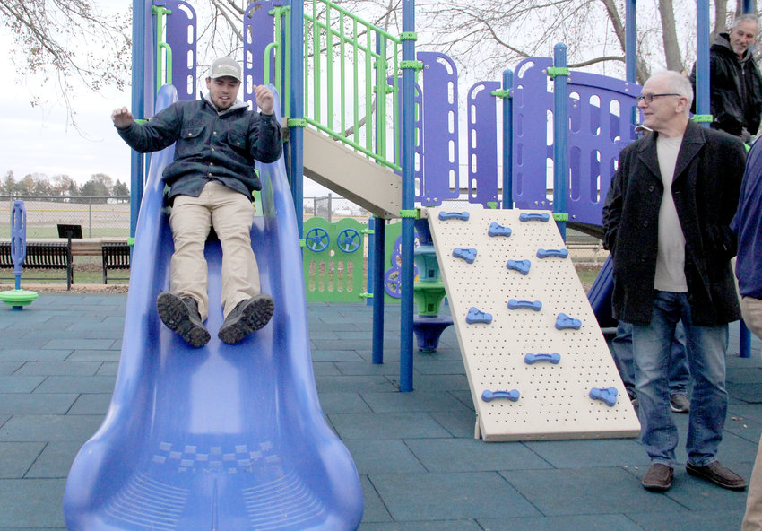 Tanner Loussaert takes a ride down Long Grove's new slide in October. He was part of the crew that installed the accessible equipment in the city park where he played as a child.