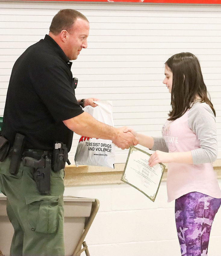 Scott County Sheriff's Deputy Ken Koehler congratulates Keira Folland for completing the DARE course.