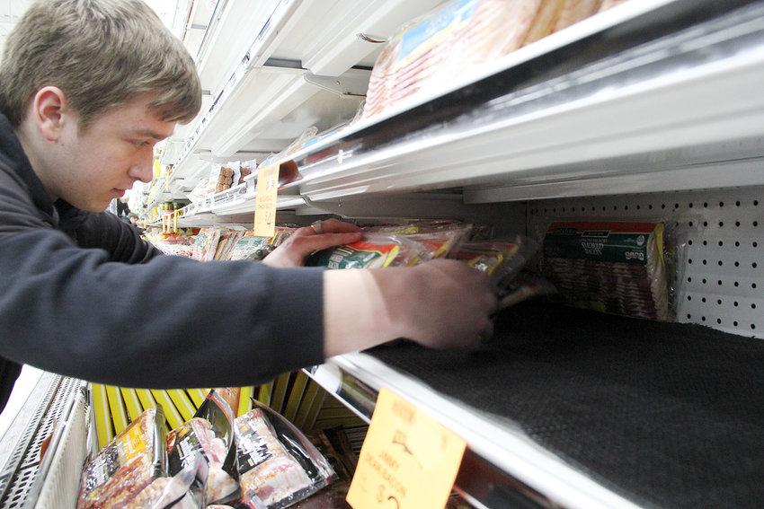 Blake Elgin restocks North Scott Food shelves Sunday.
