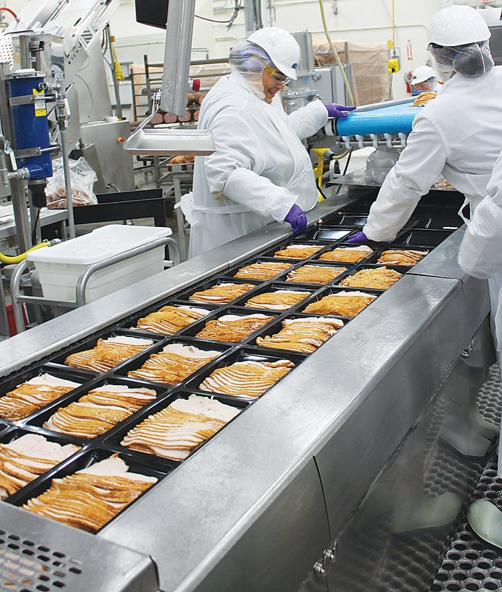 Working a line of packaged turkey breast slices are Bertha Vazquez and Madeline Rivera. The cooked breasts are sliced automatically and placed into the packaging for distribution to stores and restaurants.