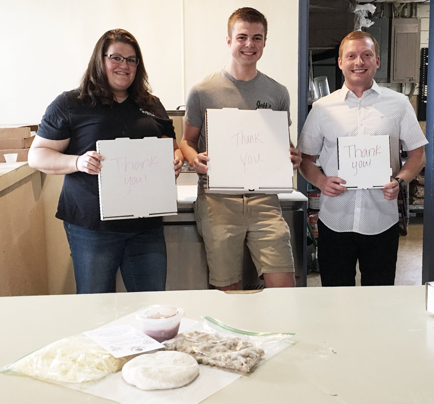 From left, Ronda Carpenter, Braden Wagner, and Austin Barclay of Idle Hour Lanes in Durant are shown holding the different sizes of pizzas you can purchase, along with ingredients that go into their pizza kits (shown on the counter in front).