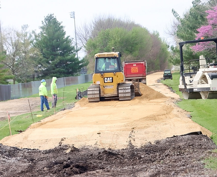 An excavator clears rail ties from Eldridge's South First Street trail.
