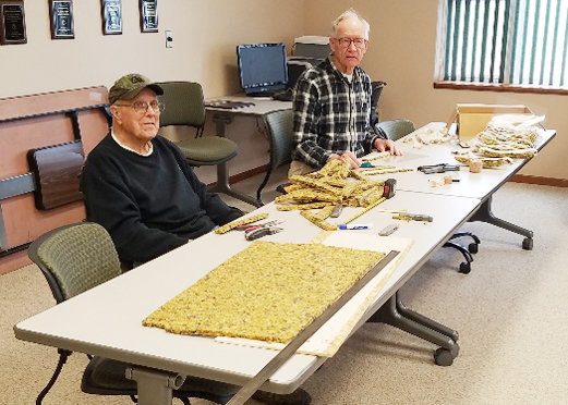Ed  Behnke (left) and Dennis Frisch are shown making homemade face shields to donate to several Emergency Medical Services (EMS) personnel in Cedar County. The shields are made with carpet padding, overhead projector overlays, elastic, staples.