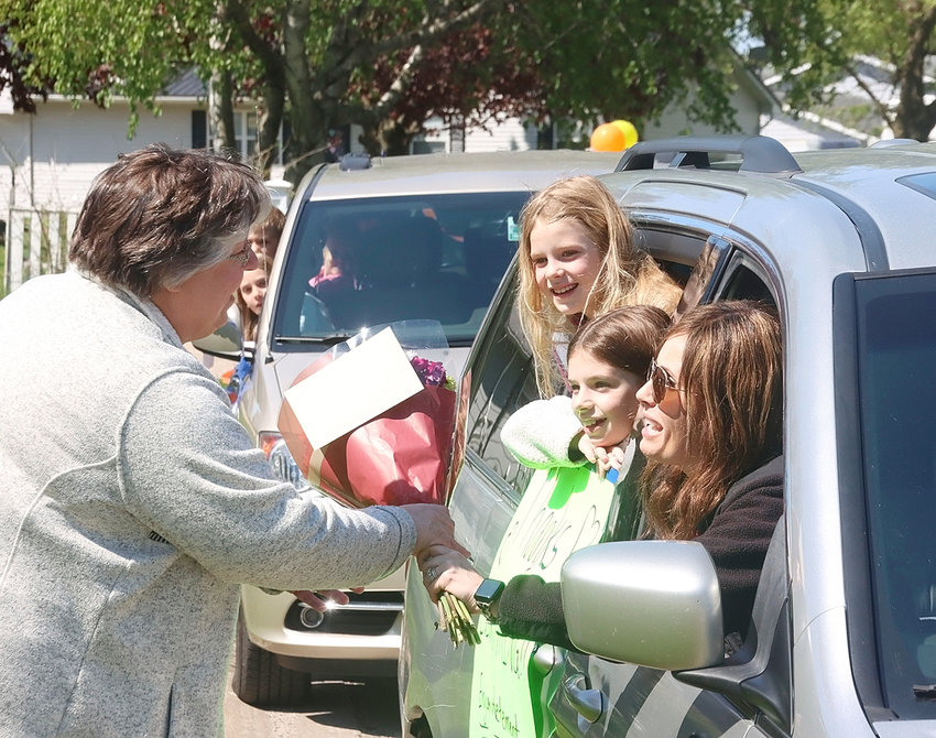 Retiring Share and Care pre-school teacher Denise Weiss welcomes warm wishes from a cavalcade of supporters, including Samantha Yanke and her children Ashley and Natalie, on Saturday, May 9.