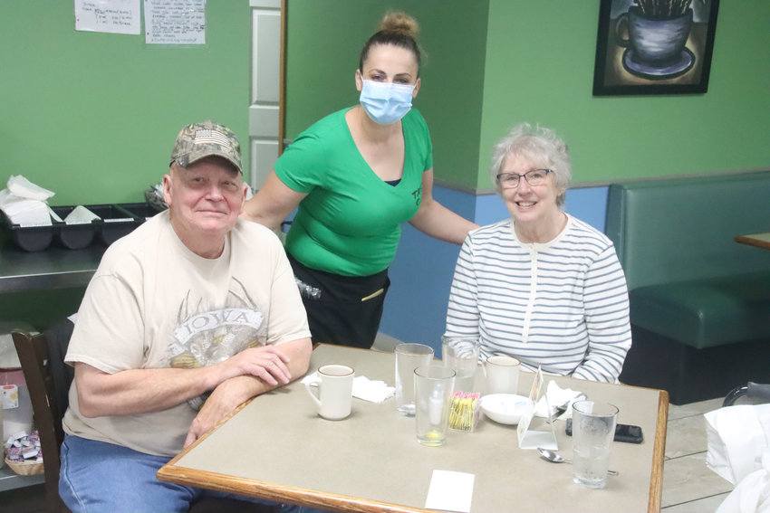 Wayne and Marilyn Griffin were happy to pose for a picture with Tuta, their favorite waitress at Tasty Cafe, when the business reopened at 5:30 a.m. on Friday.