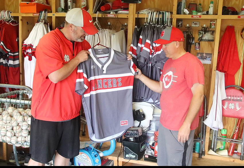 North Scott's baseball co-coaches Travis Ralfs (l) and Brad Ward started organizing the storage shed at Lancer Field after it was announced last week that there would be a baseball season. One of things the two looked over were the new gray uniforms the Lancers will be wearing.