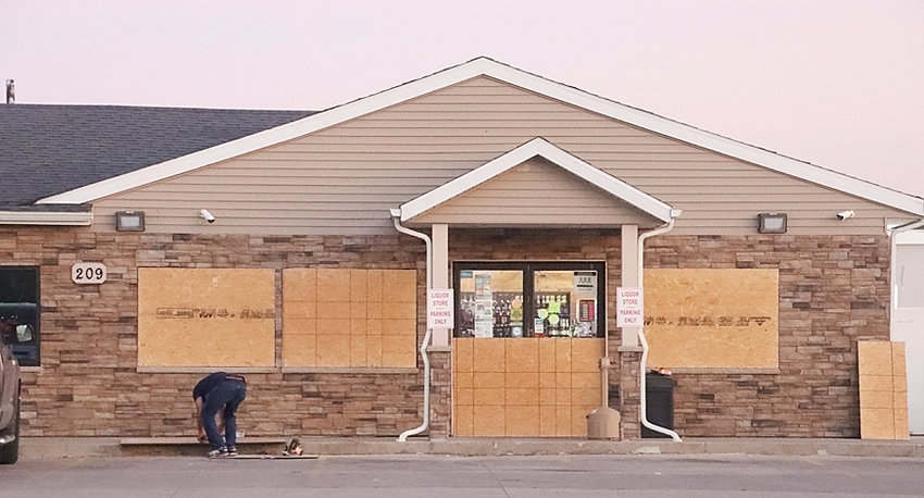 A worker boards up Eldridge Mart windows Monday in response to vandal attacks Sunday night in Davenport.