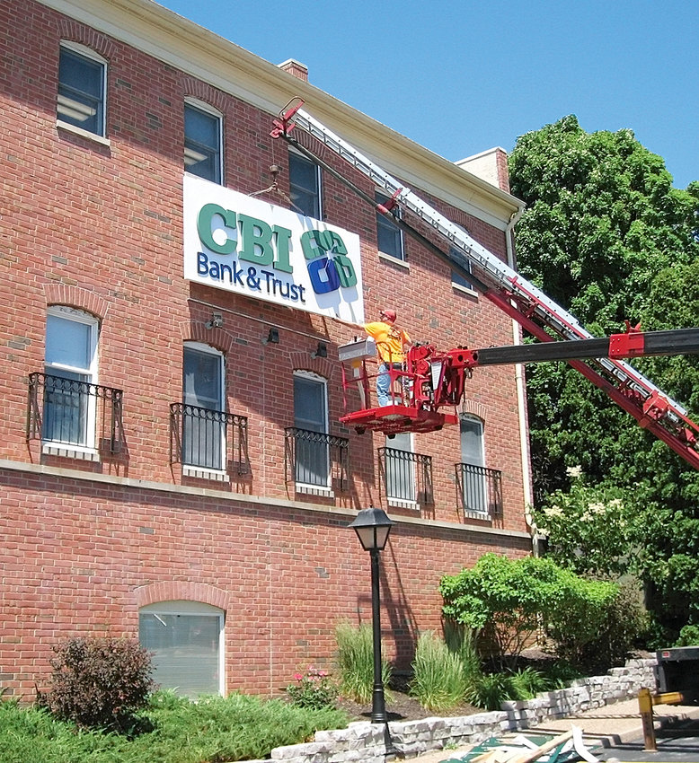 Workers change out the signs at the former Walcott Trust and Savings Bank location on East Kimberly Road in Davenport.