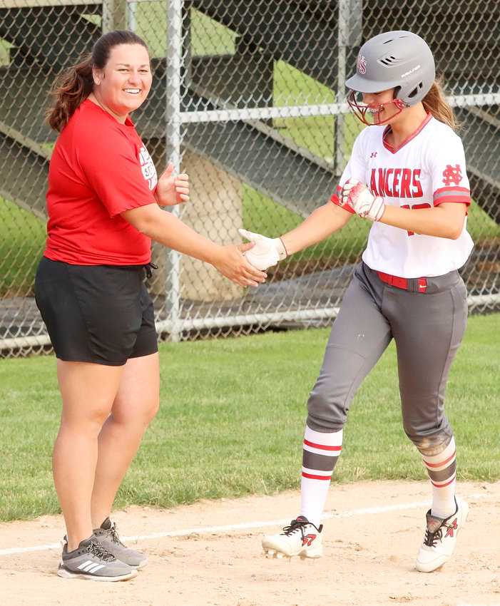 Coach Holly Hoelting congratulates Kyleigh Westlin's homer in the fourth inning against DeWitt. Her sister, Paige Westlin, scored a first-inning grand slam.