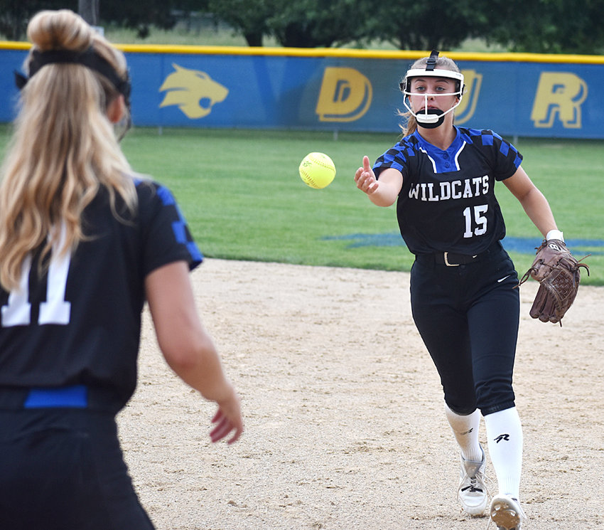 Durant second baseman Brooklyn Bullard (right) makes an underhanded toss to first baseman Halle Collier for an out in home action against North Cedar June 26.