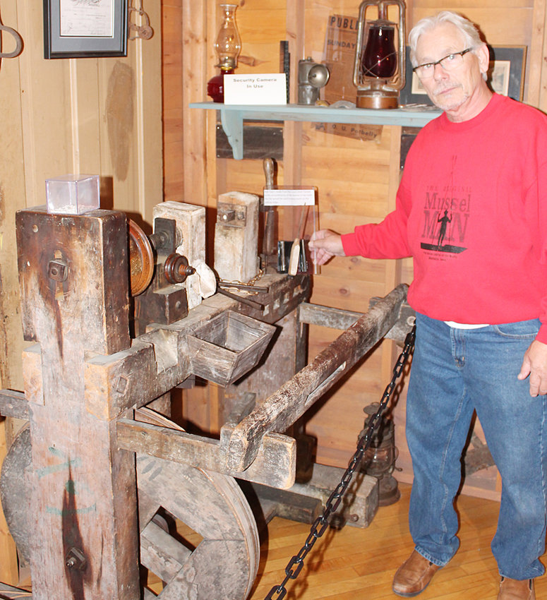National Pearl Button Museum curator Terry Eagle shows a pedal-operated button slug machine found in a barn near Wilton and now on display at the downtown Muscatine museum.