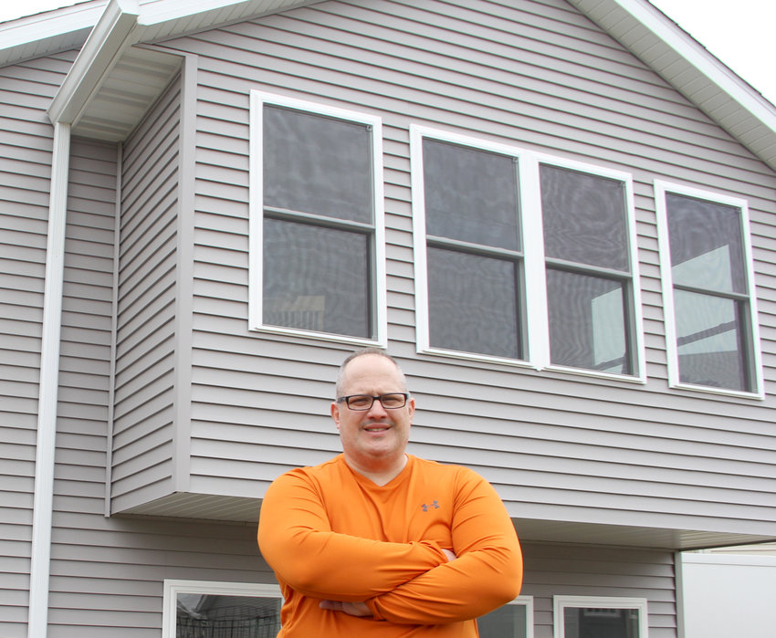 Eric Gruenhagen poses outside his West Harvest Street home addition that prompted his concerns about city housing codes. Now Gruenhagen serves on the Eldridge Board of Zoning Adjustment, which resolves such concerns.