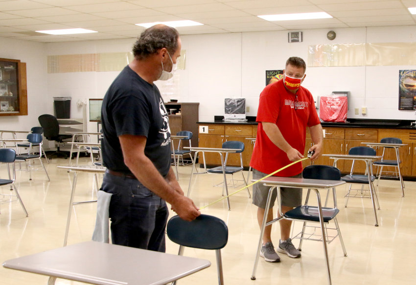 School district custodians Dan House, left, and Nate Noel, measure 6 feet between junior high classroom desks. The staff is removing non-essential tables, cabinets and other furniture to create enough room between desks.