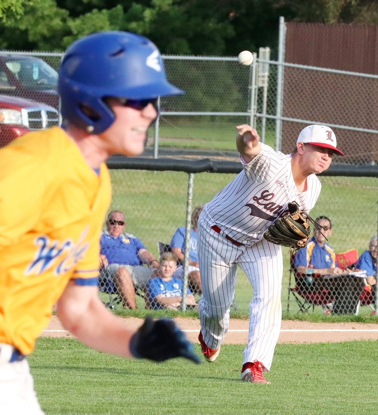 Lancer sophomore third baseman Cody Sunny fires a throw to first as he tries to nip Wildcat runner Griffin Leibold in North Scott's 3-1 victory over Davenport North on Friday.