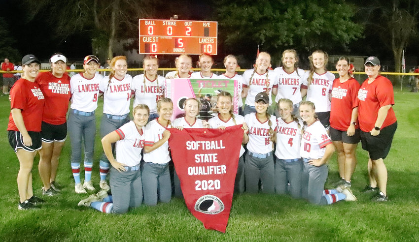 The Lancers and their coaches were all smiles as they hoisted the state qualifer banner in the outfield grass following the 10-0 win over Western Dubuque. Front (l-r): Rachel Anderson, Taylor Robertson, Sam Lee, Paige Westlin, Kyleigh Westlin, Carley Bredar and Natalie Naber. Back: Asst. coach Stephanie Burke, head coach Holly Hoelting, Brooke Kilburg, Kaylee Gerardy, Ryann Cheek, Kinsey Newman, Sydney Skarich, Drew Lewis, Shelby Spears, Maddy McDermott, Kate Hayes, asst. coach Hallie Eller and asst. coach Christy Dalton.