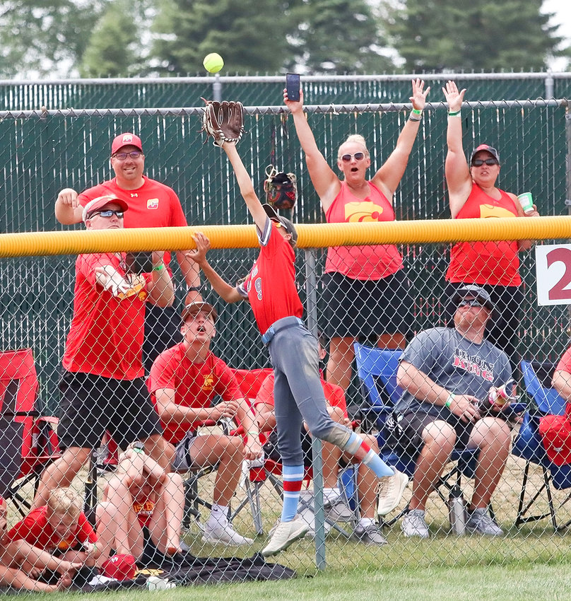 With Carlisle fans waiting in anticipation, North Scott centerfielder Brooke Kilburg goes high over the fence to try and catch this long fly off the bat of Meredith Hoffman. Kilburg got a glove on the ball, but couldn't keep it inside the park as Hoffman notched a three-run home run in her team's 8-3 semifinal victory.
