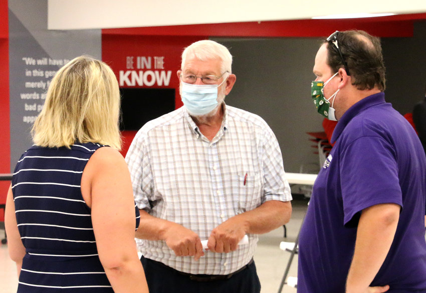 North Scott school board chairman Glen Keppy speaks with Carrie and Scott LaPlante after the forum. The couple commended the district for engaging families in the return-to-learn plan.