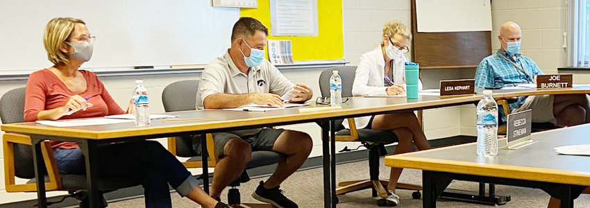 Members of the Durant School District board and administration are shown above during a regular school board meeting Aug. 10. From left, board members Carla Whitlock and Travis Bullard, board secretary Lesa Kephart, and Superintendent Joe Burnett are shown wearing masks during the meeting, a visual that will become the new normal when the school year begins Aug. 26.