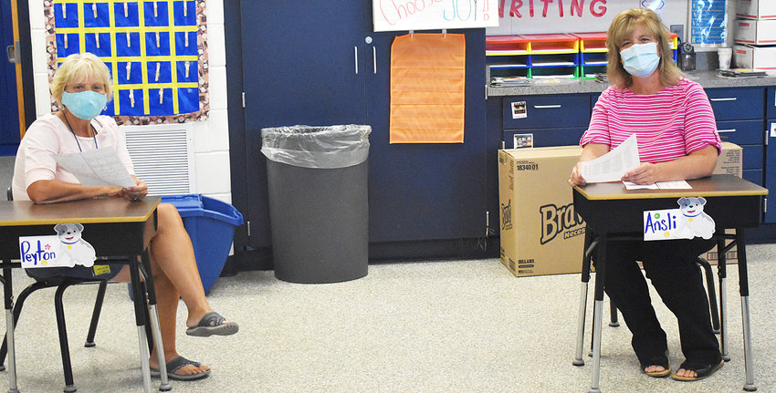Wilton Elementary School teachers Lori Petersen (left) and Melanie Drake are shown communicating in the upcoming COVID-19 world that will be the 2020-2021 school year. Desks and tables in elementary schools will be socially distanced as best they can, plus all staff and students will begin the year wearing face coverings.
