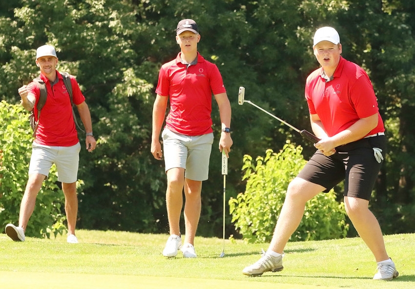 Capping a good day on the course, North Scott senior Collin Harmon (r) watches his birdie putt drop on this final hole of Wednesday's (Aug. 19) Lancer Invitational, as teammate John Dobbe (center) and coach Colin Ellis react.