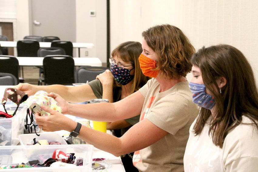 From left: Mary Staerk, Elizabeth and Olivia Richards sell masks at an Aug. 20 skate party at the Eldridge Community Center.