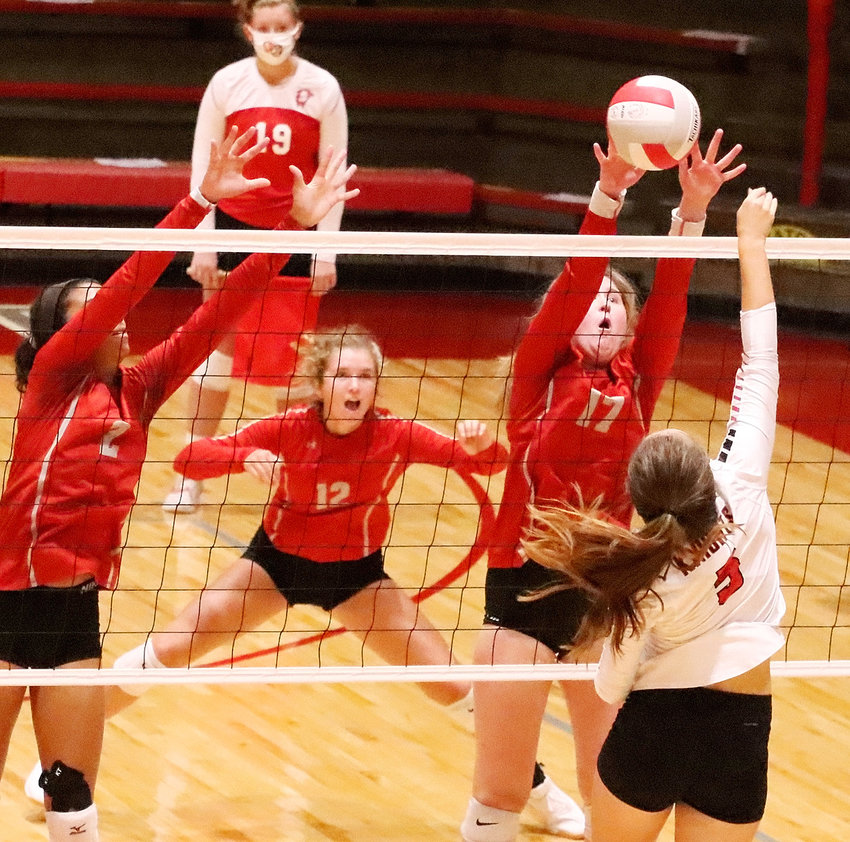 With teammates Gracie Graham (2) and Ella McLaughlin ready for a deflection, Lancer junior Lexi Richards goes up for a block in the win over Union.