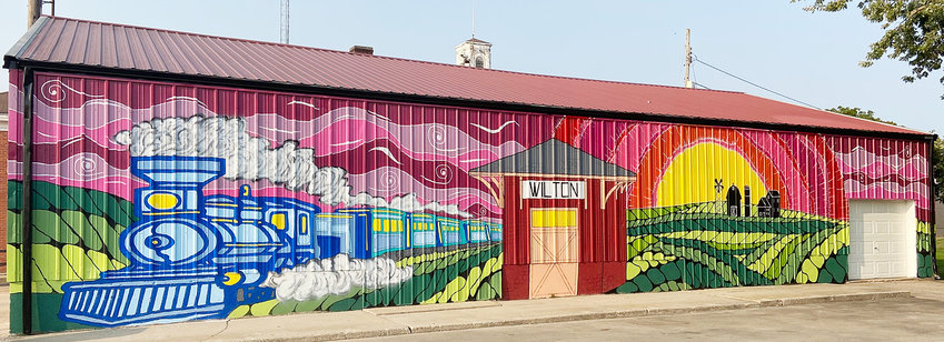 Local artist and Wilton United Methodist Church Pastor Steve Braudt recently finished a colorful mural located in downtown Wilton. The image depicting agriculture, a sunset, the Wilton Depot, and a train can be viewed on the back side of the Wilton storage shed behind City Hall, located across the street from Elder Park.