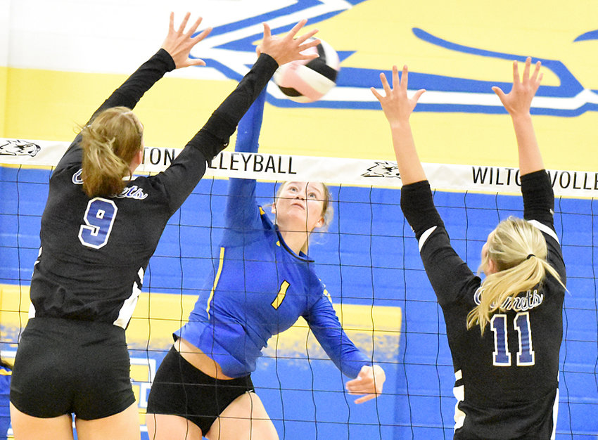 Wilton's Kelsey Drake attempts to hit between the block of West Liberty's Macy Daufeldt and Averi Goodale in RVC title game action. The Comets defeated Wilton 16-25, 25-20, 15-11.