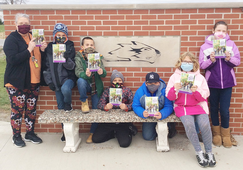 """The American Legion Auxiliary Unit 584 of Wilton recently brought safety resources to Wilton elementary students for the eighth year. Safety chairperson Jill Akers presented the books to elementary counselor Dory Smith, who will use them as a resource for fourth grade students. The """"Health Safety"""" handbooks feature information about healthy lifestyles, eating, play, environment and a healthy mind. There is information for parents, and fun activities for students to do. The """"Healthy Safety"""" handbook is published by Community Safety Net. The handbooks, pencils, reflectors and notepads given were made possible through a donation from Central Iowa Power Cooperative (CIPCO) in Wilton, Cedar Rapids and Des Moines. Pictured with the safety books are (from left) elementary counselor Dory Smith, Eli Anderson, Kypton Brown, Drew Harris, Kaden Sterner, Clarissa Spies and Kaylynn Brown."""