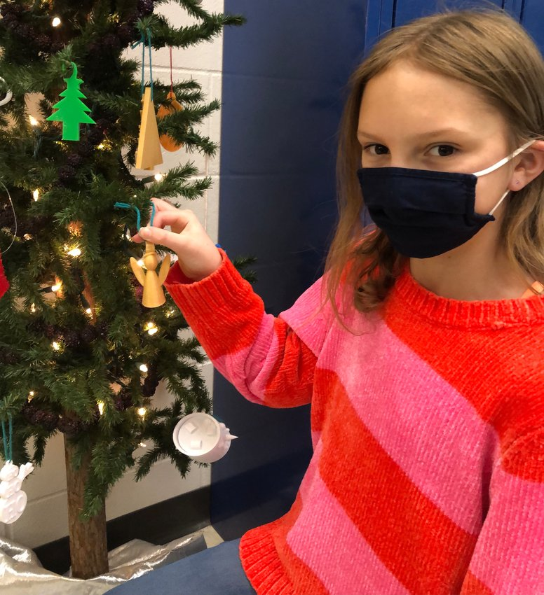 Placing her angelic ornament on a display tree at West Liberty Middle School is sixth grade Talented and Gifted student Addison Guerra.