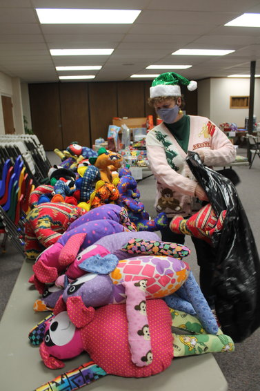 Mary Larson, a volunteer, packs stuffed animals for a family in starting to fill her bag as part of the toy gathering campaign at First Church United last week after toys were collected through the two local banks organized by the West Liberty Aquarius Club.